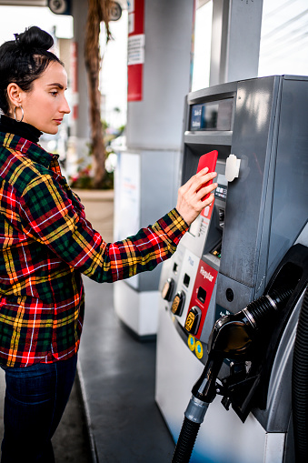 Using a mobile phone to pay for gas at a gas station.