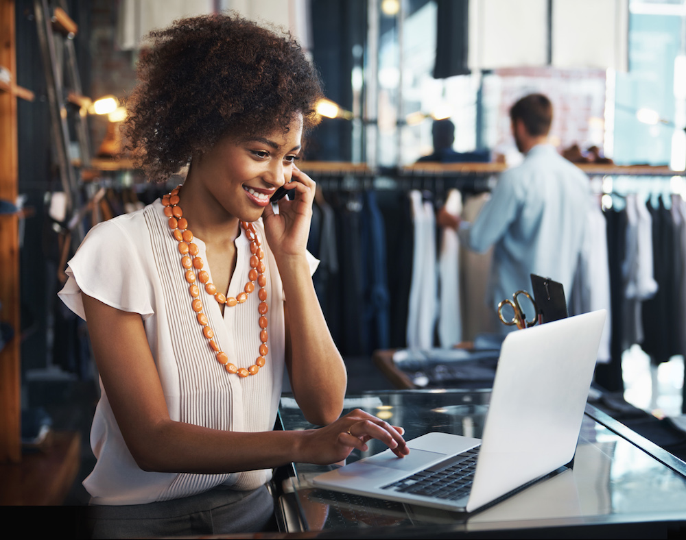 Shot of a smiling stylish woman sitting at the desk of her clothing boutique talking on her phone and looking at her laptop