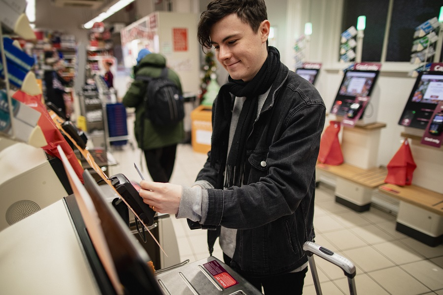 Young male adult smiling while using a self-service checkout machine while in a supermarket.
