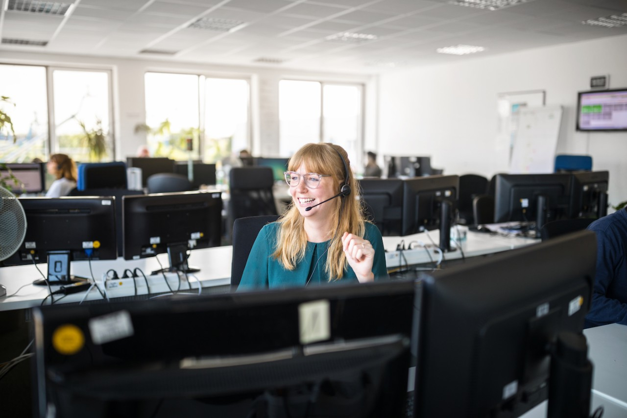 Smiling businesswoman wearing headset looking away while sitting by computers at desk in office