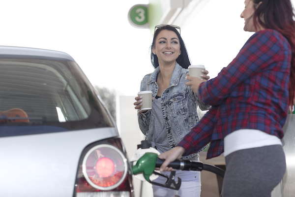 Cape Town, South Africa,Two casual females  filling up tank with petrol pump at fuel station