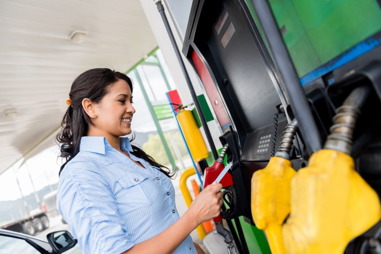 Woman at the gas station paying with credit card