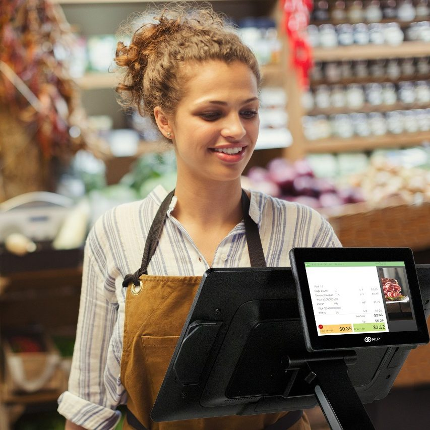 Female cashier using touch screen cash register in grocery store