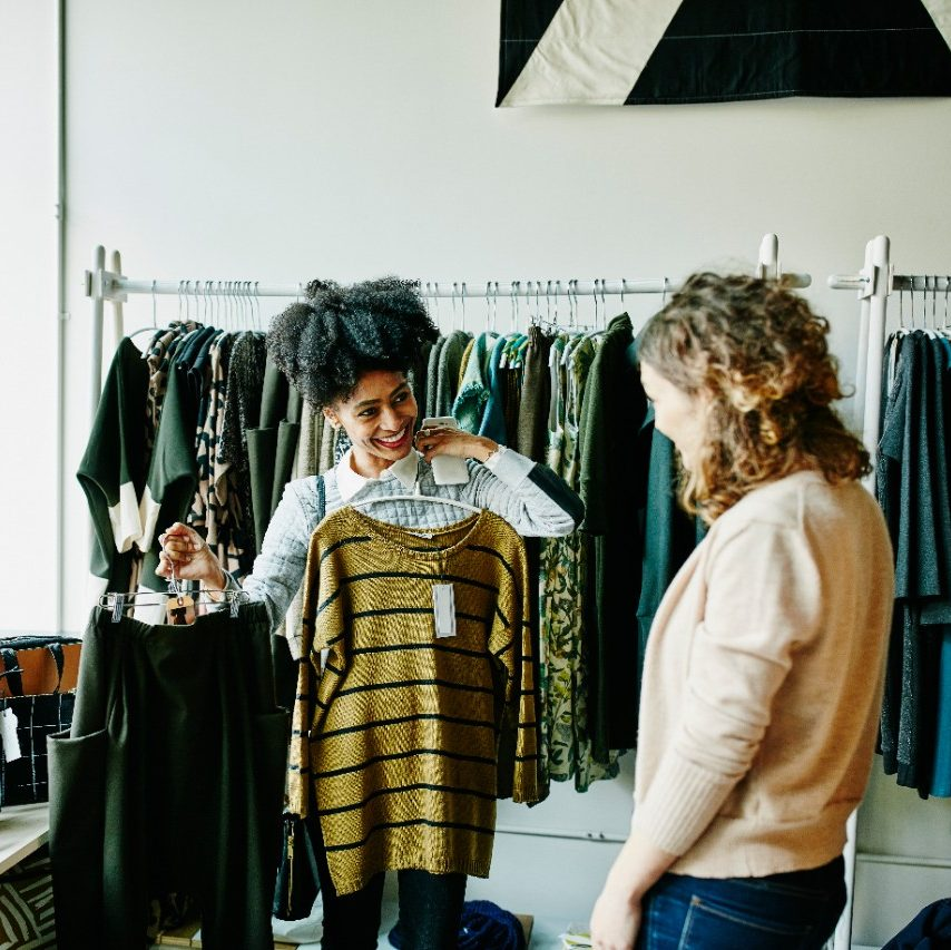 Smiling woman showing shop owner clothing options while shopping in boutique shop