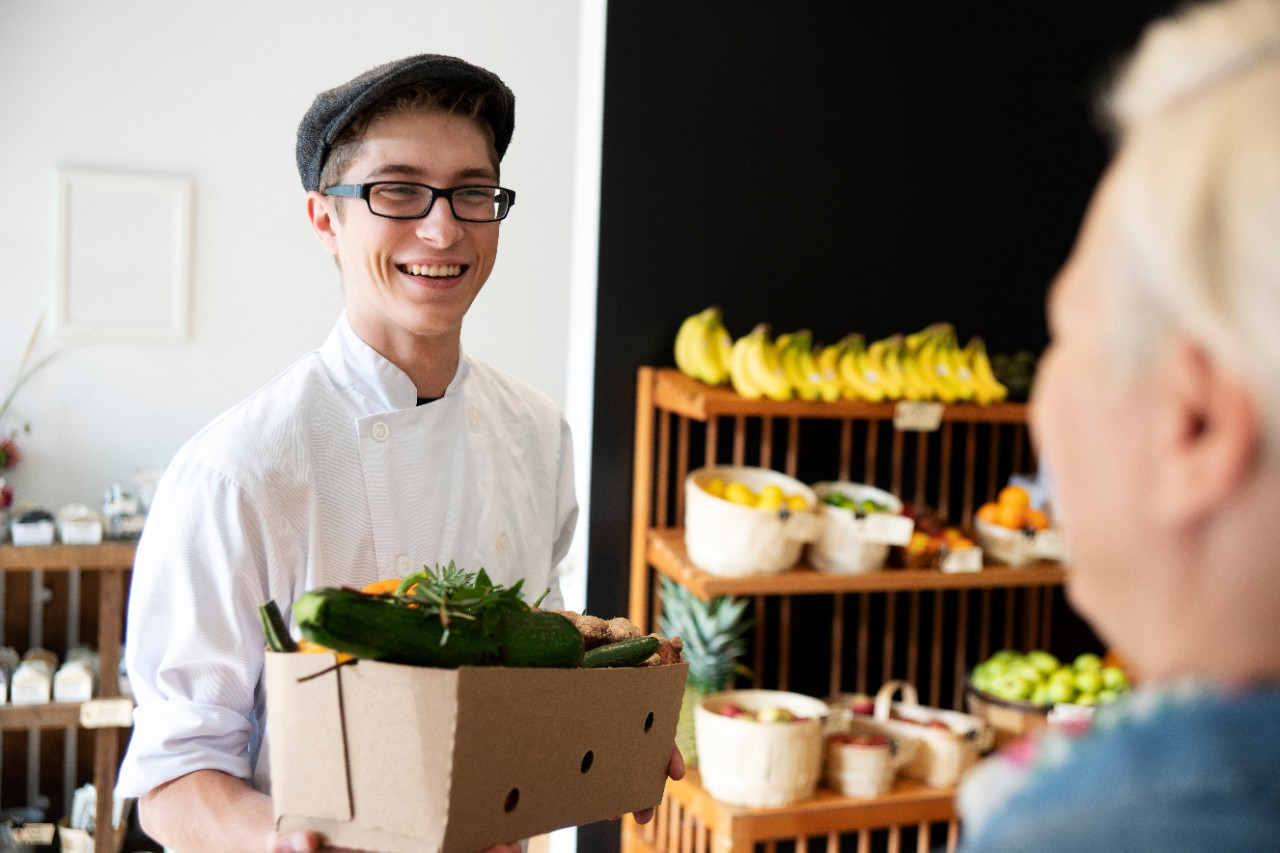 A happy young chef holding a box of organic produce talking to the manager of a small urban grocery store.