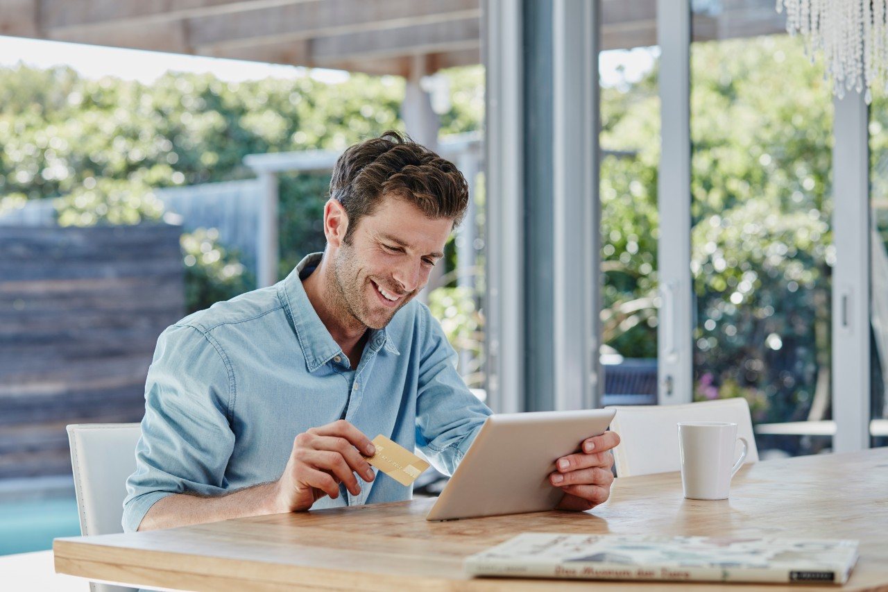 man-looking-at-tablet-with-credit-card-making-an-ecommerce-purchase