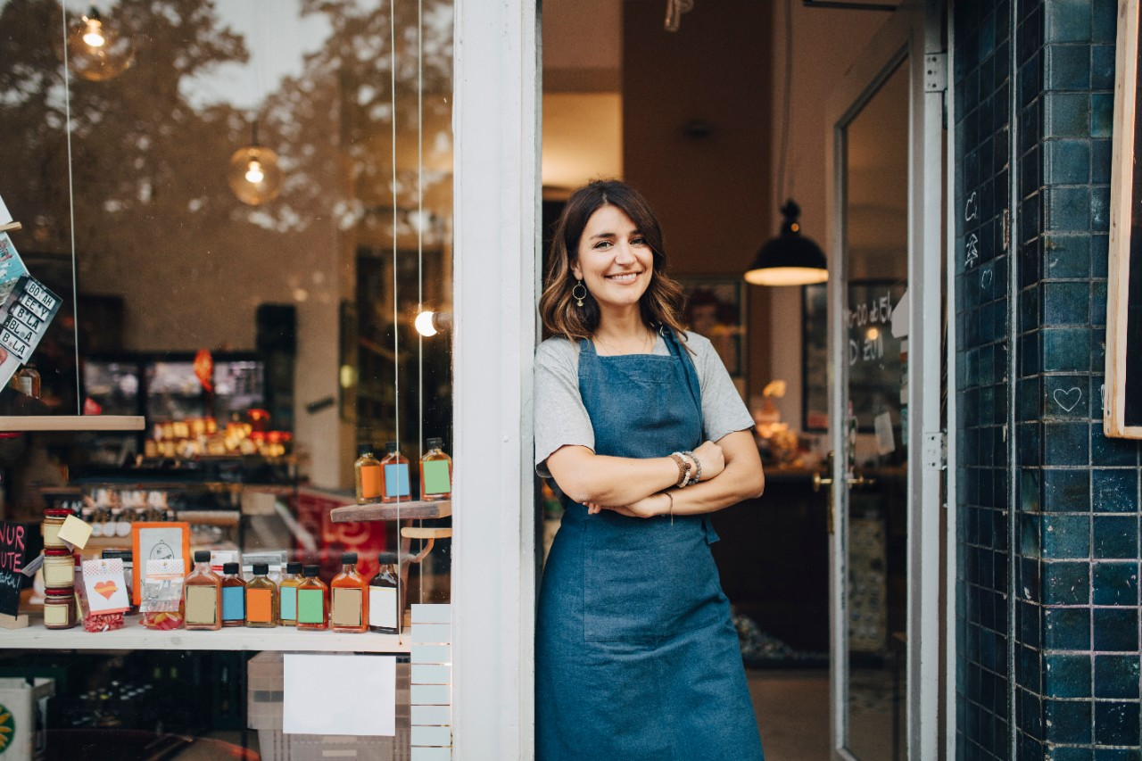 Female employee leaning on front door of store