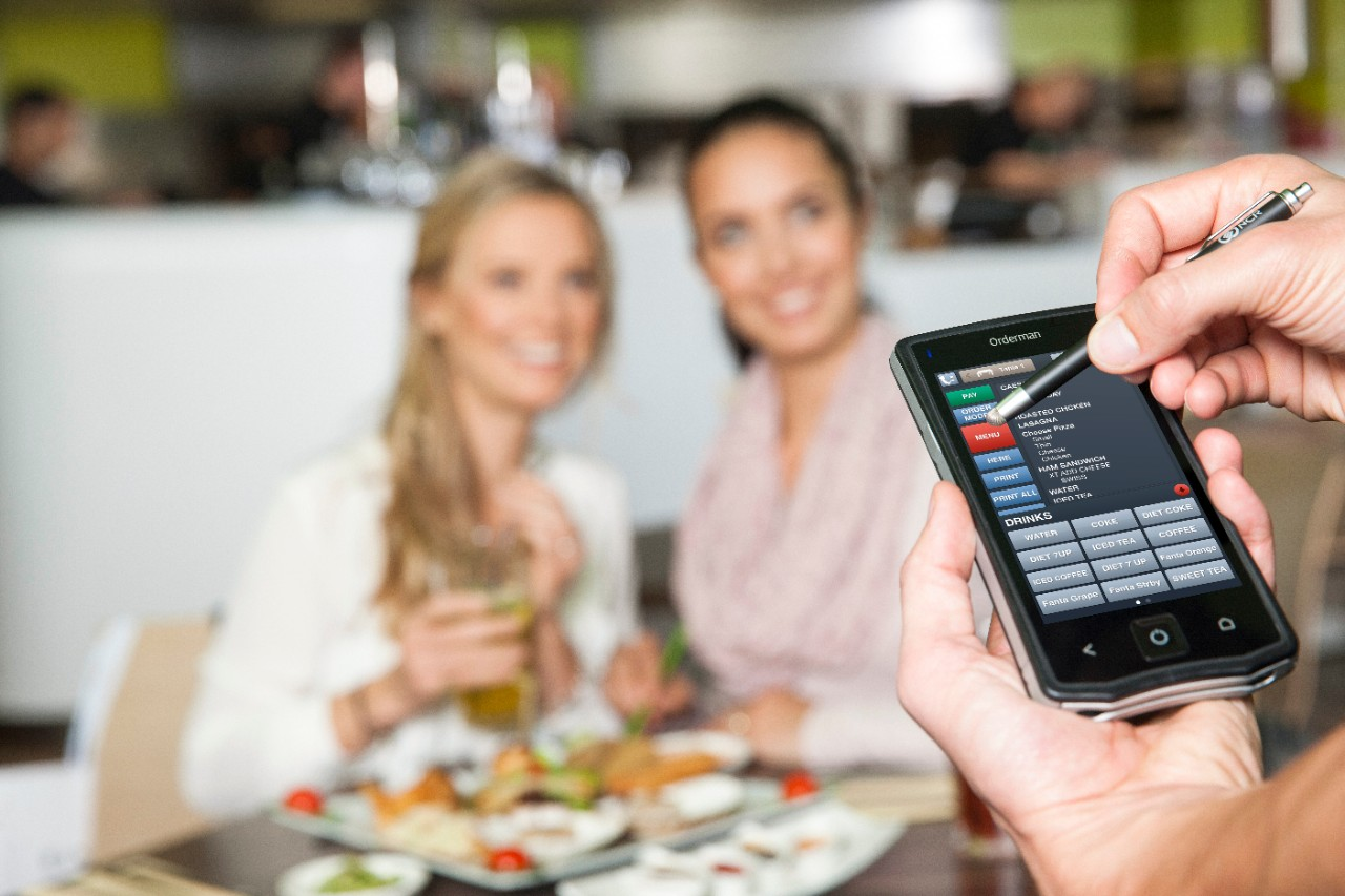 Orderman mobile pos using stylus with customers in background