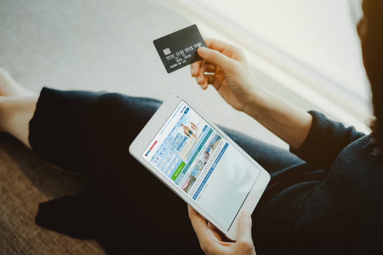 woman online ordering and planning a trip with travel on a tablet with her credit card
