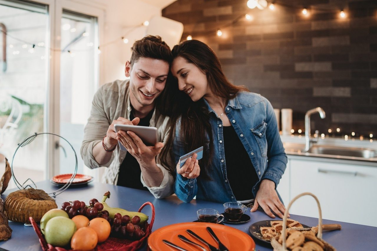Young adult couple doing online shopping together in the kitchen