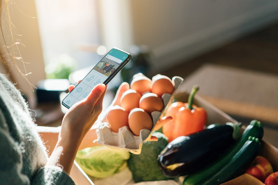 Cropped shot of woman using smartphone while picking up eggs from a delivery box filled with fresh organic fruits and vegetables at home.