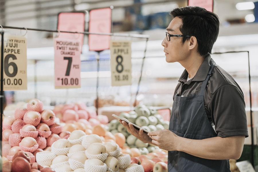 an asian chinese male store assistant checking inventory and price tag in front of fruit store department with his digital tablet
