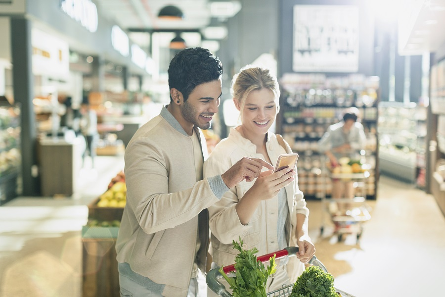 Man and woman looking at phone in grocery store