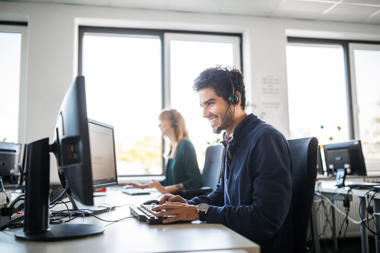 Service employees on computers in office with headsets smiling and helping