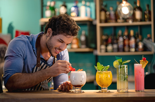 Happy barman decorating cocktails at the bar and smiling - food and drinks concepts